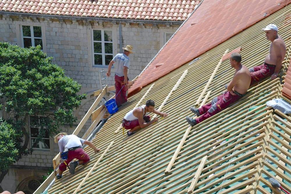 屋根の修理をする地元の大工さん。下からは見られない光景。