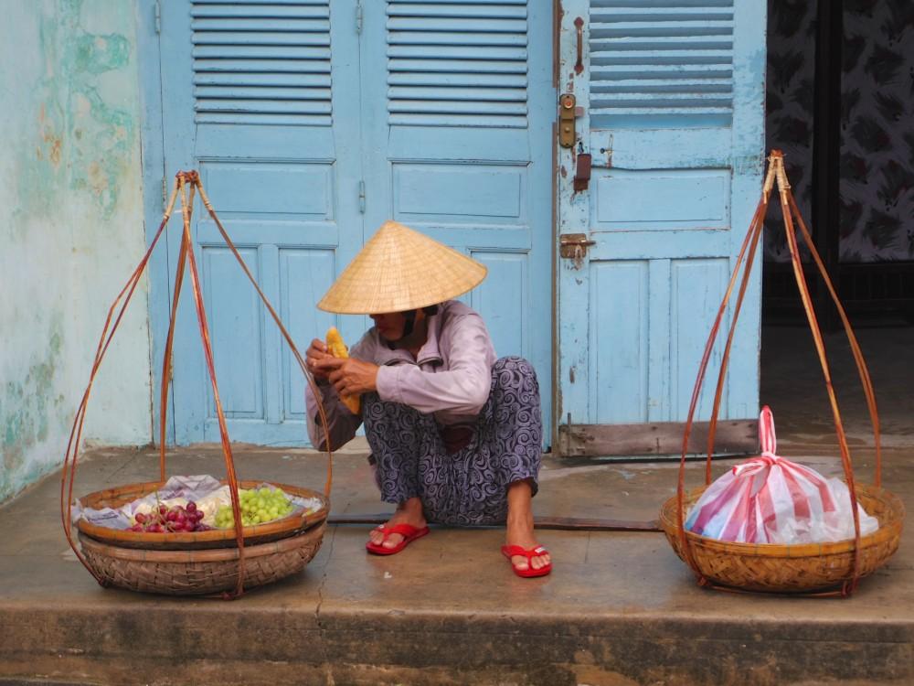 売り子のおばちゃん。ちょっと休憩してフランスパンをかじろうとしているおばちゃん。傘をかぶって篭で商品を売る姿はいかにもベトナムな光景