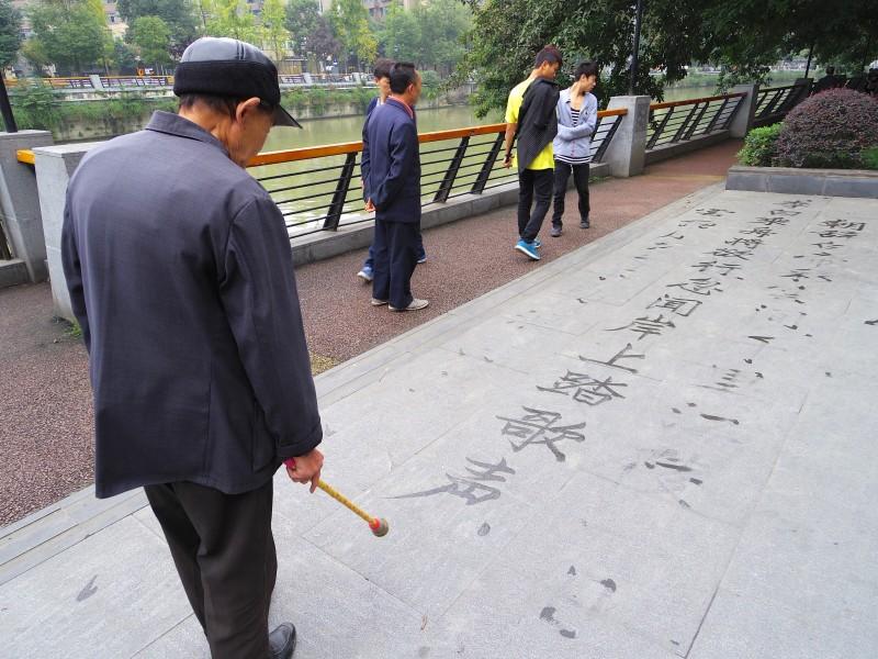 公園のおじさん。成都の公園で、大きな筆を使ってたくさんの文字を書いていた。達筆すぎる! 水だったから、すぐに乾いて消えてしまうのがもったいない