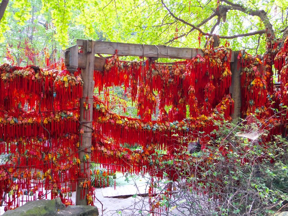 願掛けのお守り。日本では神社などで引いたおみくじを結んでいる光景をよく見るが、ここではたくさんのお守りが結ばれていた。赤い色が鮮やかでキレイ