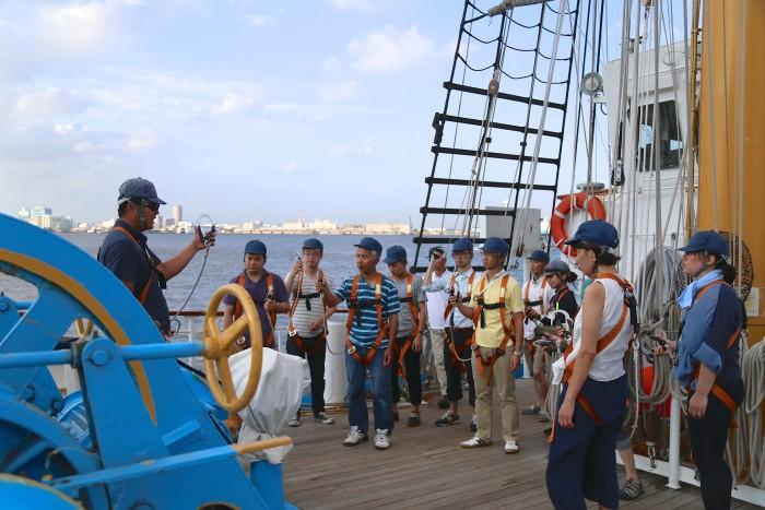 命綱となるハーネスの使い方を教わります。下は海とはいえ、10mの高さに登るので、緊張感からみんな真剣