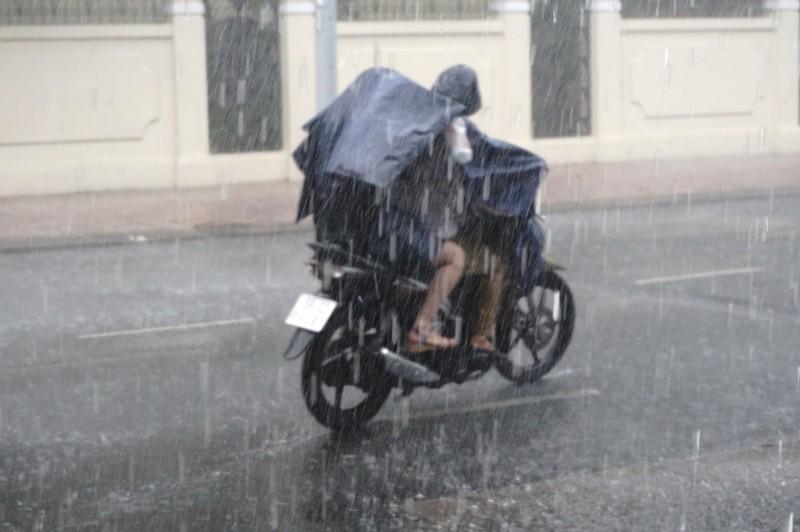 スコールの時でもレインコートを来て走っているバイクも。着脱しやすいようにレインコートはポンチョ型が多い。ま、身体濡れてますが…