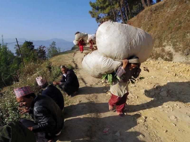 田舎の原風景。お茶を飲みながら談笑している男性たちと、大きな荷物を運んでいる女性たち。ここでは女性の方が働き者