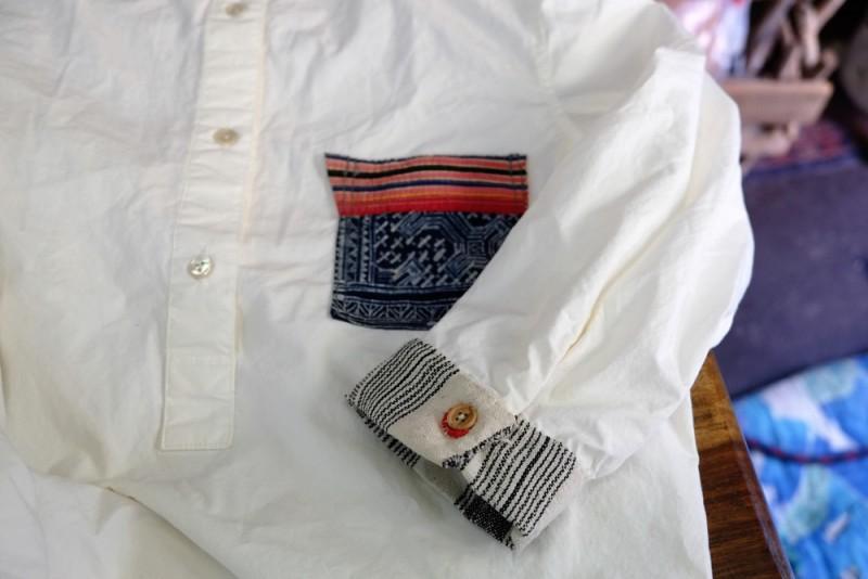 こちらはシャツのリメイク。綿のプルオーバーシャツをベースに、モン族のろうけつ染めでポケットをアレンジ。ソデ部分にはモン族のストライプ柄のヘンプ布をあしらっています。